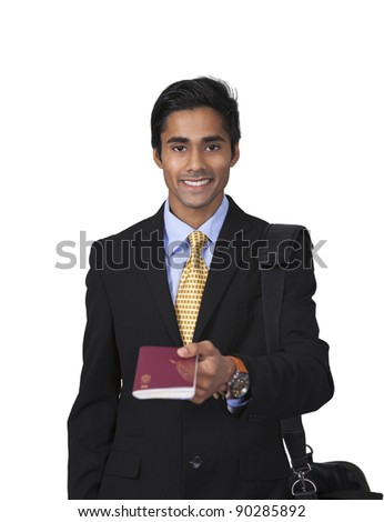 Smiling male traveler with shoulder bag showing his passport in an isolated vertical portrait - stock photo