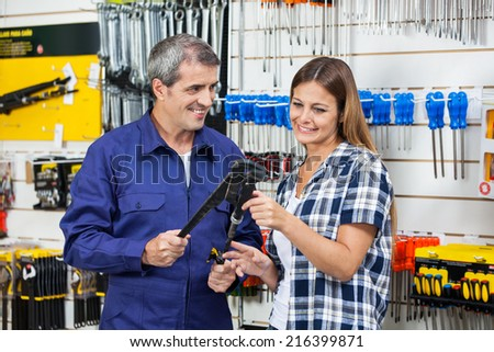 Smiling male vendor showing pliers to female customer in hardware shop - stock photo