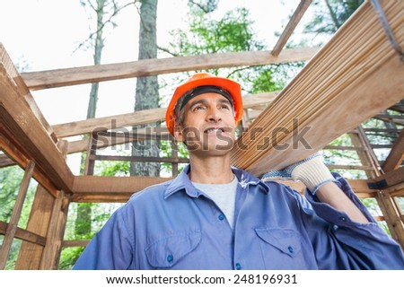 Smiling male worker carrying wooden planks at construction site - stock photo