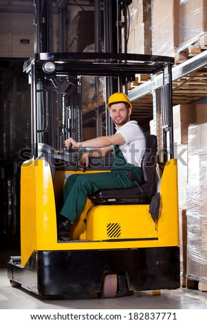 Smiling male worker in yellow forklift in the warehouse - stock photo