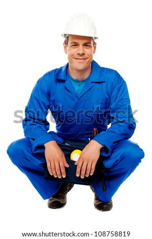 Smiling male worker wearing safety hat and relaxing, break from work - stock photo