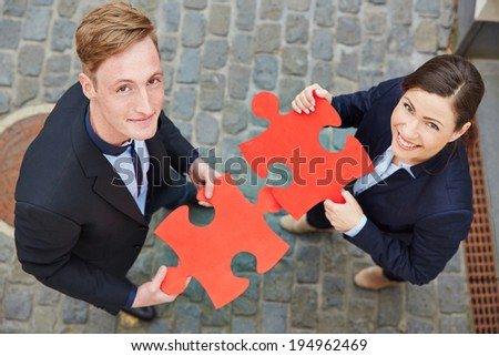 Smiling man and happy woman holding big red jigsaw puzzle pieces - stock photo