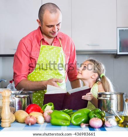 Smiling man and his little daughter cooking vegetables in domestic kitchen