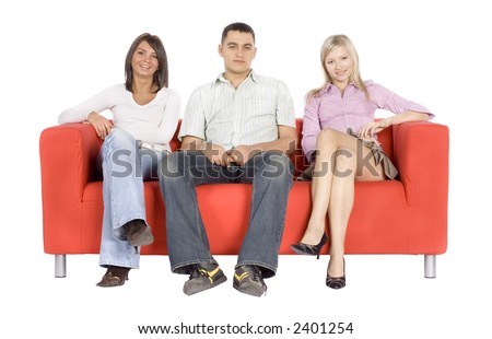 Smiling man and two women sitting on a red couch.  Isolated on white background, in studio. - stock photo