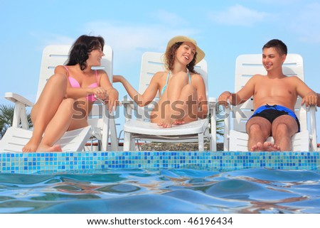 Smiling man and two young women reclining on chaise lounges near pool open-air,Talk with each other - stock photo