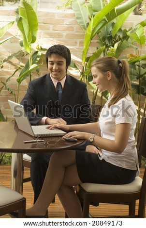 Smiling man and woman at a desk looking at a laptop computer. Vertically framed photo.