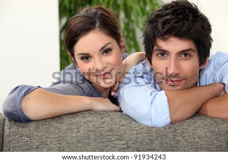 Smiling man and woman leaning on a couch - stock photo