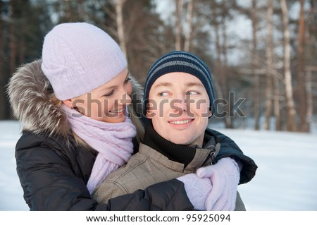 Smiling man and woman on the background of winter landscape