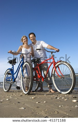 Smiling man and woman pose with bicycles on the sand near the beach. Vertical shot. - stock photo