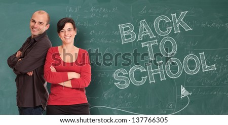 Smiling man and woman standing by a chalkboard with the words back to school - stock photo