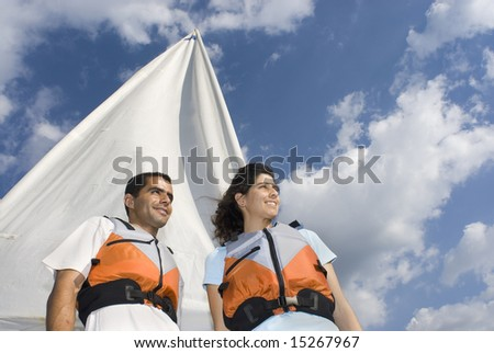 Smiling man and woman standing in front of sail staring off into distance. Horizontally framed photo - stock photo
