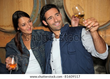 Smiling man and woman tasting wine in a cellar - stock photo
