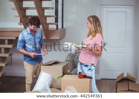 Smiling man and woman unpacking books at home - stock photo