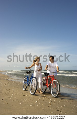 Smiling man and woman walk bicycles down the beach coast. Vertical shot. - stock photo