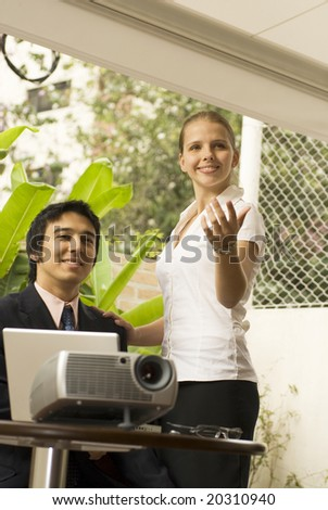 Smiling man and woman with a projector. He is seated and she is standing with her arm out. Vertically framed photo.