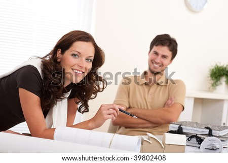 Smiling man and woman with architectural model at office