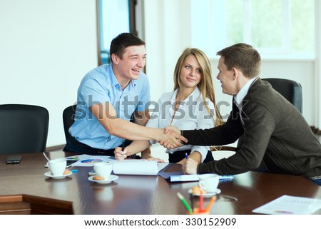 Smiling man at a business meeting shaking hands with each other in the office in the presence of a business woman. - stock photo