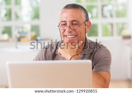 Smiling man at laptop in kitchen - stock photo