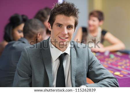 Smiling man at roulette table in casino - stock photo