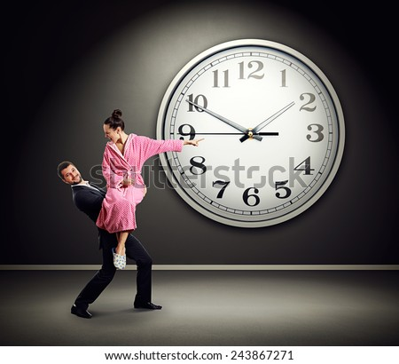 Smiling man carrying his angry wife who is screaming at the man and pointing at clock on wall over dark background - stock photo