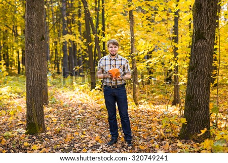 Smiling man carrying pumpkin in a park