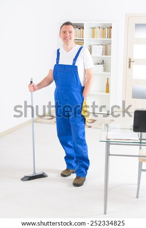 Smiling man cleaner standing with a broom at the office - stock photo