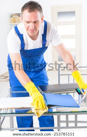 Smiling man cleaner wearing yellow gloves and cleaning office - stock photo
