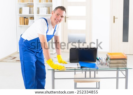 Smiling man cleaner wiping table at the office - stock photo