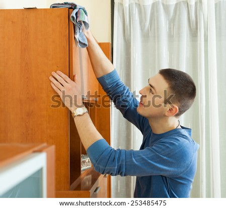 Smiling man cleaning wooden furniture with rag - stock photo
