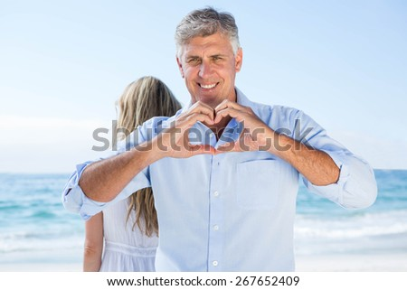 Smiling man doing heart shape with his hands at the beach - stock photo