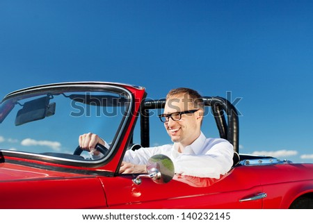 Smiling man driving a red cabriolet convertible against a sunny blue sky, closeup portrait - stock photo