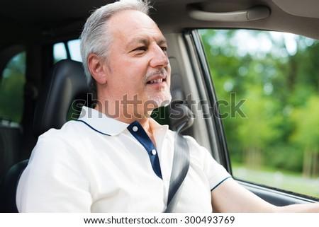 Smiling man driving his car - stock photo