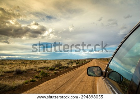 Smiling man driving through wilderness on straight dirt road - stock photo
