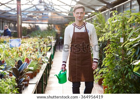 Smiling man gardener in glasses and brown apron standing and holding watering can in orangery - stock photo