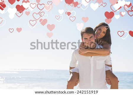 Smiling man giving girlfriend a piggy back looking at camera against valentines heart design - stock photo