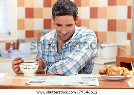 Smiling man having continental breakfast in his kitchen with a newspaper