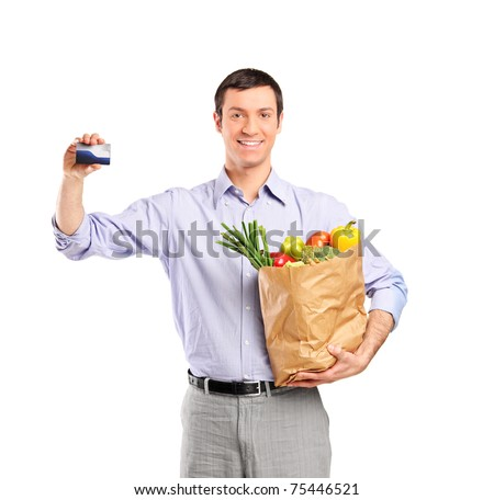 Smiling man holding a credit card and a bag full with vegetables isolated on white background - stock photo