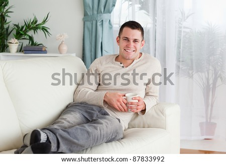 Smiling man holding a cup of coffee in his living room - stock photo