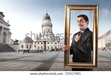 Smiling man holding a frame with monument on the background - stock photo