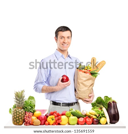 Smiling man holding an apple and paper bag with food products, posing behind a table full of fruits and vegetables