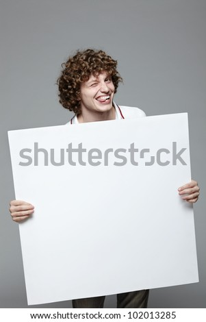Smiling man holding blank banner over gray background - stock photo