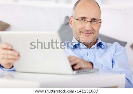 Smiling man holding laptop while leaning on the couch at home - stock photo