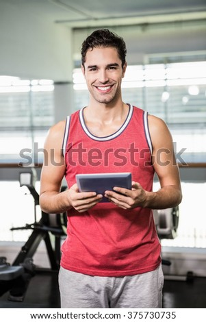 Smiling man holding tablet in the gym