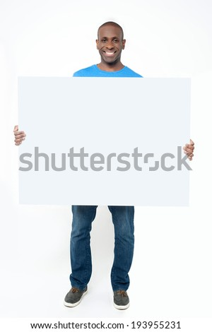 Smiling man holding up blank white billboard - stock photo