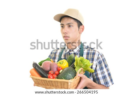 Smiling man holding vegetables with fruits