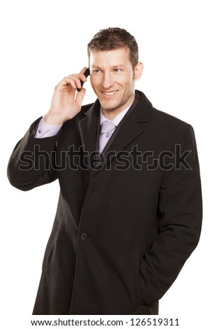 smiling man in a coat telephones on white background