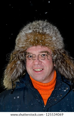 Smiling man in a fur hat - stock photo