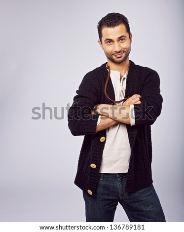 Smiling man in a studio with arms crossed and copyspace left - stock photo