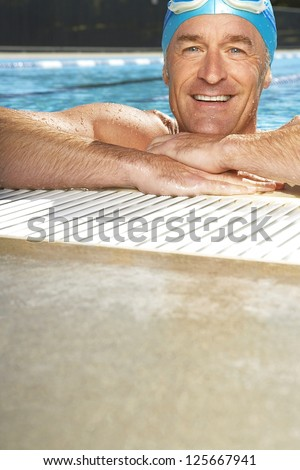 smiling man in a swimming wearing swimming cap and goggles on his head, his arms resting at the edge of swimming pool - stock photo