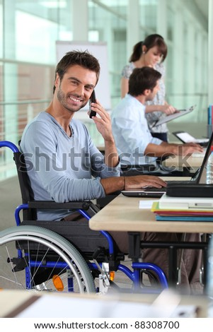 Smiling man in a wheelchair working in an office - stock photo
